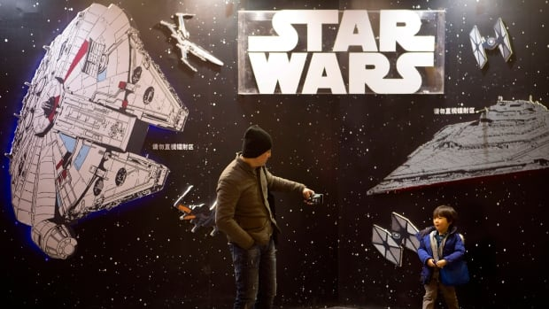 A man takes a photo of his son at a Star Wars promotional display in Beijing, Jan. 9, 2016. The Chinese market is less familiar with the franchise and its history compared to North America.