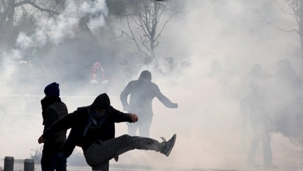 A protester kicks a tear gas canister back to police during clashes in Pristina, Kosovo, on Saturday.