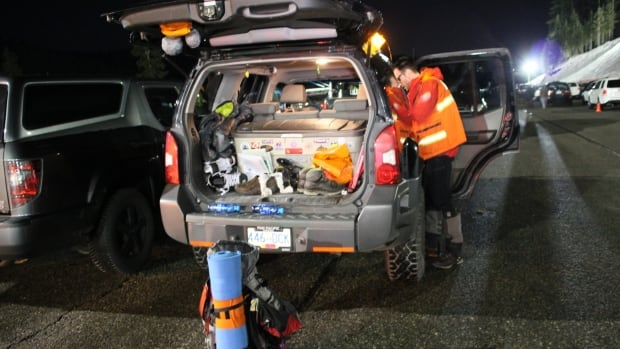An NRS volunteer gears up for a search in the Cypress Mountain Resort ski area parking lot on Saturday night.
