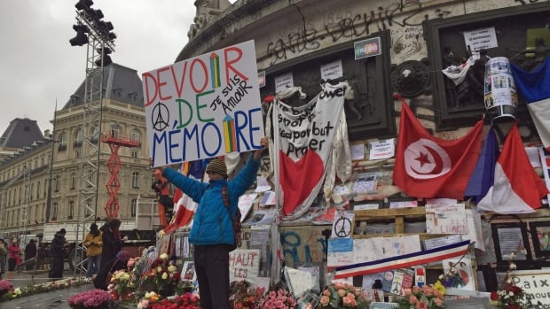 A man holds a sign that reads 'Duty to Remember' at the statue in Place de la République in Paris during Sunday's memorial ceremonies.