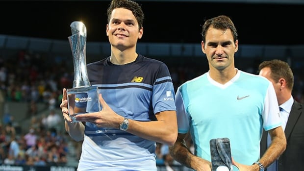Milos Raonic holds the winners trophy while Roger Federer holds the runner up trophy after the Mens Final during day eight of the 2016 Brisbane International at Pat Rafter Arena on January 10, 2016 in Brisbane, Australia.