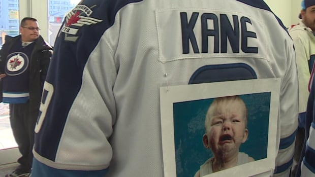 "On Sunday, Winnipeg Jets fans dressed in outfits to express how they feel about Evander Kane, calling him a ""baby"" and carrying around ""money phones."""