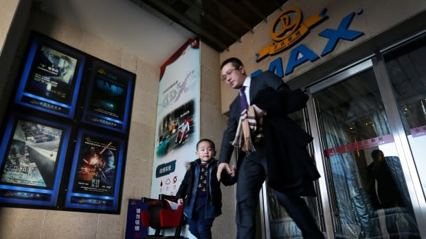 A man and his son exit the cinema at the Wanda Group building in Beijing on Tuesday. Wanda Group has announced it is buying Hollywood's Legendary Entertainment, the maker of films such as Batman and Inception, for $3.5 billion US in the first Chinese acquisition of a major U.S. film company.