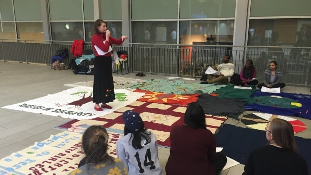 Facilitator Gabrielle Fayant leads participants through the blanket exercise originally developed by KAIROS.