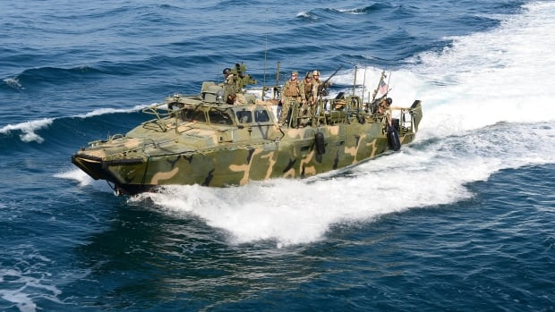 A riverine patrol boat from Costal Riverine Squadron 2 escorts the guided-missile cruiser USS Bunker Hill while in the Arabia Gulf in a 2014 photo provided by the U.S. Ten sailors aboard two U.S. Navy riverine patrol boats were seized by Iran in the Gulf on Jan. 12.