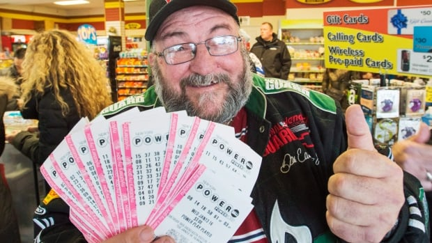 Robert Charbonneau, from St-Donat, Que., holds up $1,000 worth of Powerball tickets for himself and his friends at a convenience store on Tuesday in the border town of Champlain, N.Y. Those who don't want to wait in line are using websites like TheLotter.com, which buys tickets on their behalf, even though some lottery officials and Powerball organizers warn against using such unregulated services.