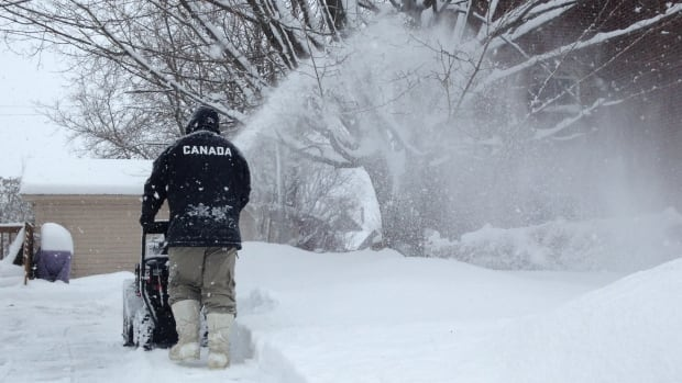 A Fredericton resident clears a path out of the latest snowstorm in Fredericton.