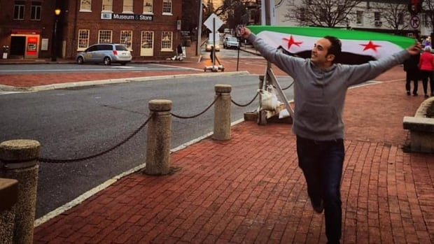 Mostafa Hassoun draped in the flag of the Syrian opposition, runs down Main Street in Annapolis, Md. 'I thought he might get shot,' said one local woman who has been helping the Syrian refugee. Hassoun arrived in the U.S.  about seven months ago and is struggling to adapt to life in a country where many have been reluctant to welcome new arrivals from Syria.