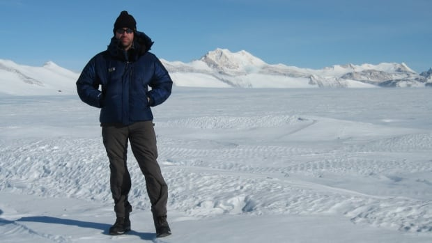 Glaciologist Martin Siegert stands on an ice bed in Antarctica