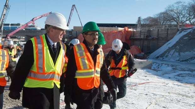 Infrastructure Minister Amarjeet Sohi (right) and Ottawa Mayor Jiim Watson tour the site of a future light rail transit station Wednesday. The new Liberal government wants to accelerate federal spending on municipal transit and housing projects, despite the downturn in the economy.