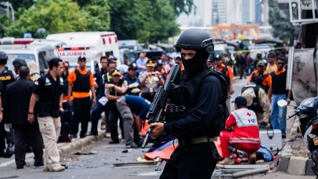 An Indonesian policeman stands guard in front of a blast site in Jakarta on Jan. 14, 2016. A third victim has died two days after the attacks.