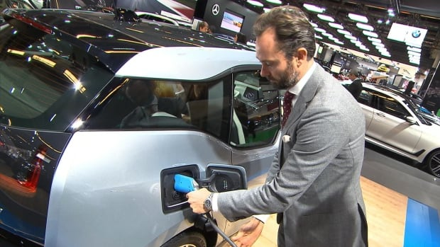 Marc Belcourt of BMW demonstrates the charging of an electric car at the Montreal International Auto Show at Palais des congrès.