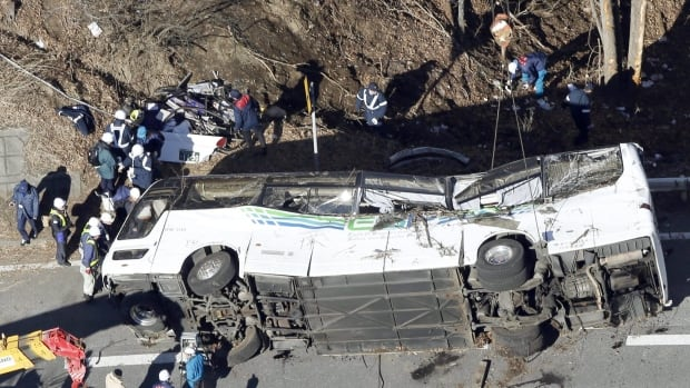 Investigators work near a damaged bus after it was transferred by crane onto a road in Karuizawa, Nagano prefecture on Friday. The overnight tour bus on its way to a ski resort careened off a mountain road.