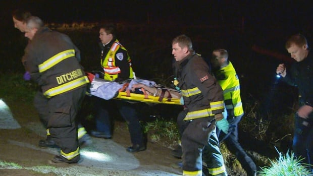 Emergency responders transport a man found in the waters off near Kitsilano Beach on Thursday night.