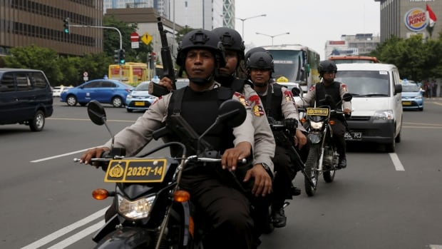 Indonesian policemen ride motorcycles as they patrol near the bomb blast site at Thamrin business district in Jakarta on Friday.