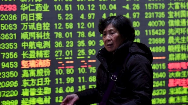 An investor walks past an electronic screen showing stock information at a brokerage house in Hangzhou, Zhejiang Province, China on Friday. China stocks dropped more than 3 percent on Friday, capping another tumultuous week in which the Shanghai Composite index tried and failed to stay above lows hit during last year's summer crisis.