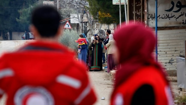 Members of the Syrian Red Cross stand near aid vehicles loaded with food and other supplies that entered the besieged Syria town of Madaya, northwest of Damascus, earlier this week.