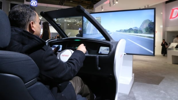 Arshad Khalakdina tests a Denso driver-assist simulator at the North American International Automotive Show. The GM consultant drives a six-speed shift, but imagines his children will grow up in a world of fully autonomous vehicles.