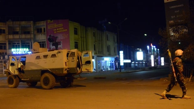 Army forces drive near a hotel where gunmen attacked in Burkina Faso's capital of Ouagadougou on Friday.