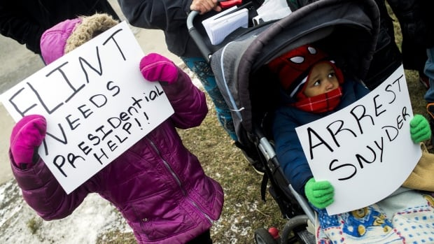 Cousins Rayanna Connor, 5, left, and Damoni Cheeks, 2, both of Flint, Mich., hold up signs asking for presidential help and calling for the arrest of Gov. Rick Snyder at a water crisis rally on Saturday, Jan. 16, 2016.
