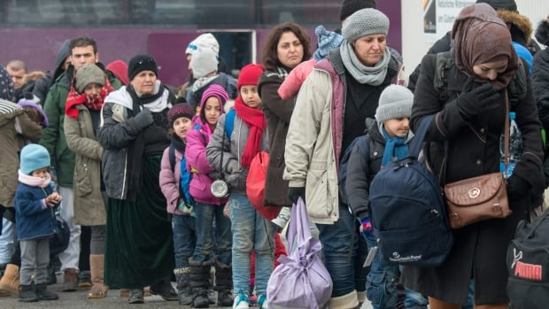 Refugees walk to a chartered train at the railway station of Passau, Germany, on Jan. 5. Many women and girls making the journey to Europe, especially those travelling alone, have been subject to sexual harassment or violence, Amnesty International says.