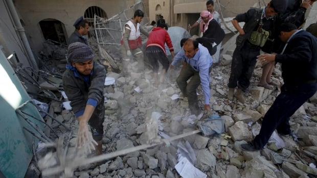 Policemen and medics remove debris Monday as they search for victims at the site of a Saudi-led air strike on the police headquarters in Yemen's capital Sanaa.