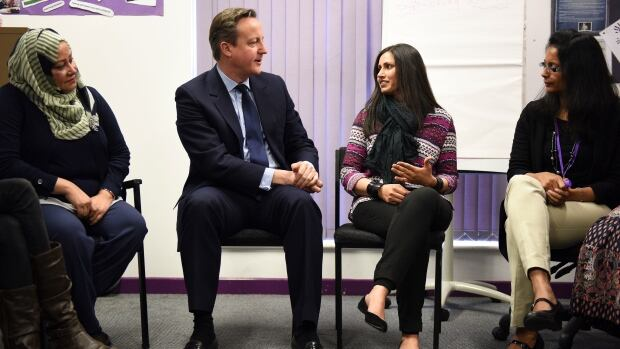 U.K. Prime Minister David Cameron speaks with women attending an English language class during a visit to the Shantona Women's Centre in Leeds, Britain, on Monday.  Some migrants to Britain who cannot pass an English test within 2½ years of arriving may not be allowed to stay, Cameron said.