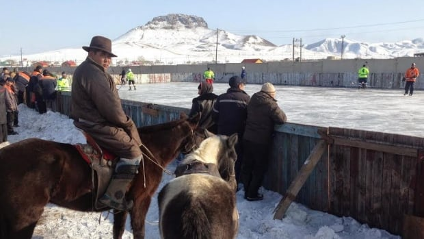 A local herdsman has the best and only seat in the house for a game of pick-up hockey in Zuun Kharaa, Mongolia.
