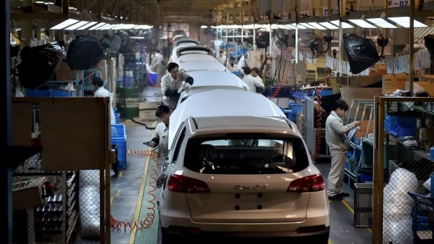 Chinese workers on the assembly line of the X5 SUV of Zotye Auto in Hangzhou in Zhejiang province are shown on Monday.