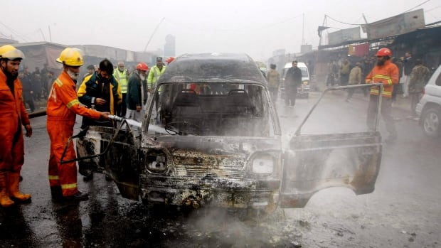 Pakistani firefighters try to extinguish a vehicle on fire following Tuesday's suicide blast in Peshawar.