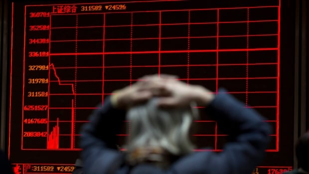 A woman reacts to plunging stocks on the Shanghai Composite Index at a brokerage in Beijing. China's growth for the fourth quarter is at six-year low and for all of 2015 at a 25-year low.