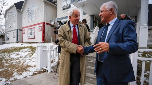 Immigration, Refugees and Citizenship Minister John McCallum, left, meets with Calgary Catholic Immigration Society CEO Fariborz Birjandian, right, at the Margaret Chisholm Resettlement Centre in Calgary.