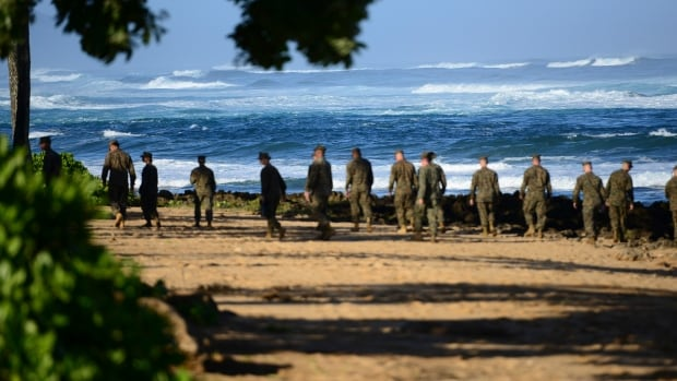 A group of Marines walk the beach outside the Haleiwa Incident Command Post in Haleiwa, Hawaii, during search efforts for 12 missing Marines, in this handout photo taken Jan. 18.