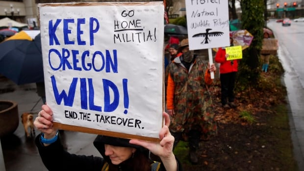 Renee Irvin holds a sign during a rally against the occupation of the Malheur National Wildlife Refuge by Ammon Bundy and his armed followers, while joining the rally at the Federal Building in Eugene, Ore., on Tuesday.
