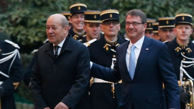 French Defence Minister Jean-Yves Le Drian, left, walks with U.S. Secretary of Defence Ashton Carter before meeting in Paris on Wednesday. The pair joined their German, British, Italian, Australian and Dutch counterparts to develop strategies on their collective efforts against ISIS, with Canada not included in the meeting.