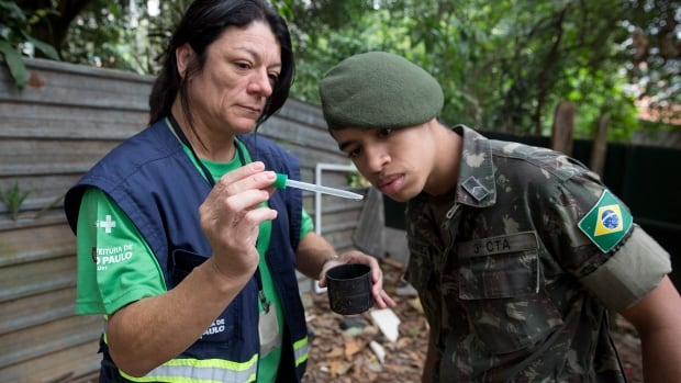 A health agent from Sao Paulo's public health secretary shows a soldier Aedes aegypti mosquito larvae that she found during clean up operations against the insect that transmits Zika virus.