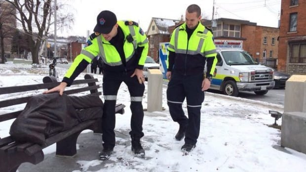 Paramedics approach a statue on a bench in a photo from the Hamilton Paramedics Twitter page. The statue in Hamilton is getting a lot of attention from paramedics as a recent blast of wintry weather has resulted in calls about a homeless person sleeping on a bench.