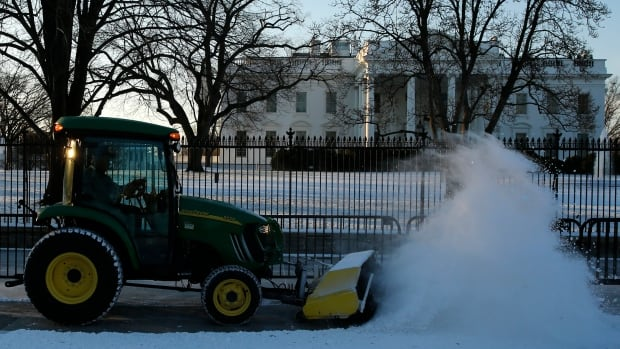 A worker plows snow from the sidewalk in front of the White House on Thursday. Following a light dusting of snow, Washingston is now preparing for a blizzard.