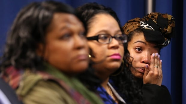 Bridget Anderson, right, wipes away a tear as DeKalb County District Attorney Robert James announces Thursday that a grand jury indicted DeKalb County Police Officer Robert Olsen for shooting and killing of her boyfriend Anthony Hill.