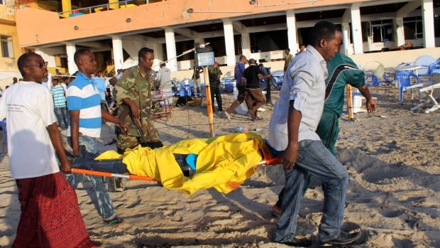 Relatives carry away a dead body from the beach following the overnight attack on the beachfront restaurant in Mogadishu.