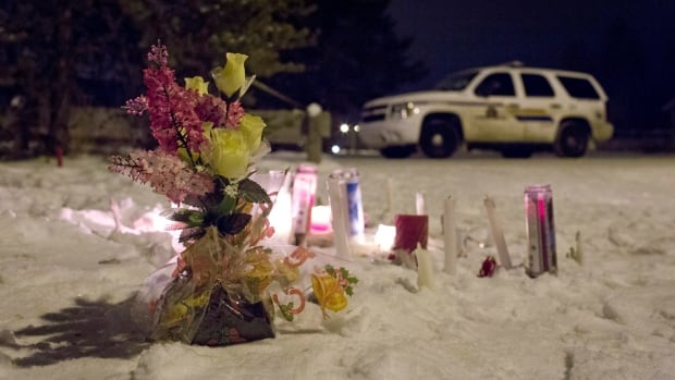 Candles and flowers were placed as a memorial near the La Loche, Sask., junior and senior high school as police investigate the scene of a daytime shooting at the school that left four people dead.