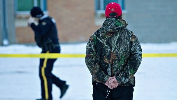 A man holds a rosary as police investigate the scene of a shooting at the La Loche Community School in norther Saskatchewan on Saturday, Jan. 23, 2016. The shooting took place on Friday, leaving four people dead.