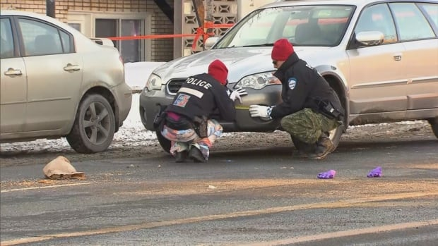 Police carefully go over the scene where a man was hit by a vehicle this afternoon in Villeray.