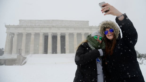 Two women take a selfie in front of the Lincoln memorial during a snow storm Saturday in Washington, D.C.