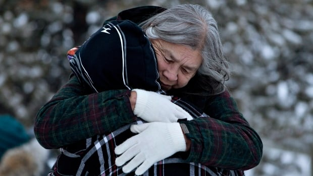 Residents console each other at the memorial near the La Loche Community School in La Loche, Sask., where four people were killed and seven others injured.