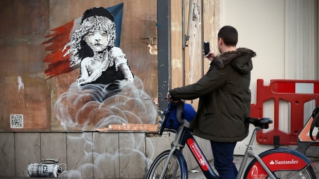 A passing cyclist snaps a photo of a new Banksy artwork opposite the French embassy in London on Monday. The graffiti artwork depicts the young girl logo from the musical Les Misérables, but with tears in her eyes as CS gas moves towards her, a criticism of the use of teargas in a French migrant camp in Calais.