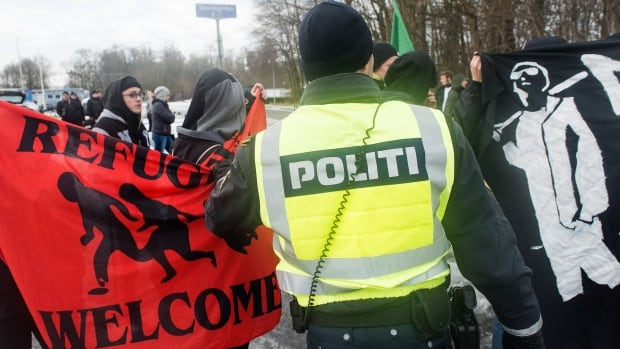 A police officer tries to separate pro- and anti-migrant protesters at the Danish-German border on Jan. 9 in Krusaa, Denmark. The Danish parliament voted Tuesday to seize migrants' valuables to help pay for their stay in the country.