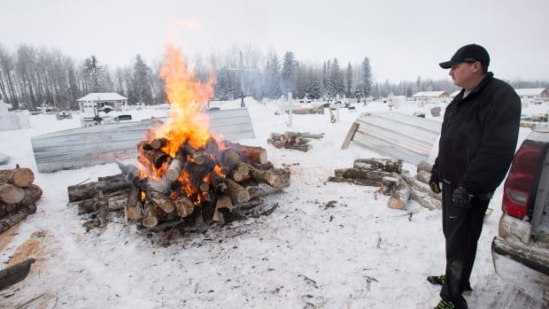Gerald Moise, father of shooting victim Dayne Fontaine, 17, looks on as a fire is lit at the cemetery in La Loche, Sask., on Monday. A  boy, 17, is accused of killing Fontaine and three others.
