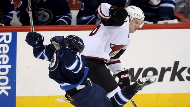 The Winnipeg Jets' Alexander Burmistrov, left, is tripped by Arizona Coyotes' Michael Stone during the third period Jan. 26 at the MTS Centre. The Jets won the game 5-2.