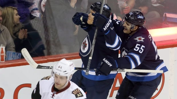 Winnipeg Jets' Nikolaj Ehlers (27) and Mark Scheifele (55) celebrate after Ehlers scored as Arizona Coyotes' Kevin Connauton looks on during the first period Tuesday at the MTS Centre.